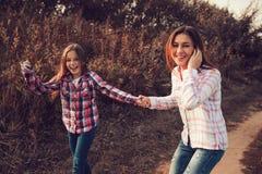 愉快的母亲和女儿步行的在夏天调遣 家庭室外消费的假期 免版税库存照片
