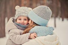 愉快的母亲和女儿步行的在多雪的冬天 免版税库存照片