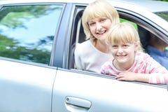 愉快的母亲和女儿汽车的 免版税库存图片