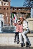 愉快的母亲和女儿游人在米兰,意大利上升的旗子 库存图片