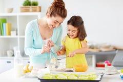 愉快的母亲和女儿烘烤松饼在家 免版税库存照片