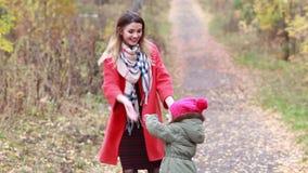 愉快的母亲和女儿获得使用的乐趣在公园在秋天 股票录像