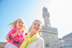 愉快的母亲和女婴在佛罗伦萨,意大利 免版税库存照片