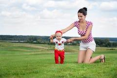 愉快的母亲和女婴户外 免版税图库摄影