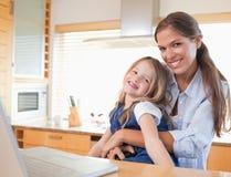 愉快的母亲和她的使用膝上型计算机的女儿 免版税图库摄影