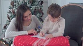 愉快的母亲和她的儿子文字信件给圣诞老人 库存图片