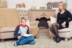 愉快的母亲和她的儿子文字信件给圣诞老人 免版税库存照片