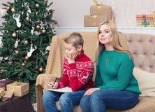 愉快的母亲和她的儿子文字信件给圣诞老人 图库摄影