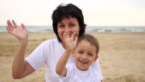 愉快的母亲和她的儿子,坐海海滩,微笑和摇他们的在慢动作的手 股票录像