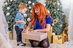 愉快的母亲和她的孩子围拢与圣诞节装饰 库存照片