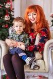 愉快的母亲和她的孩子围拢与圣诞节装饰 库存图片