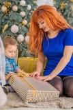 愉快的母亲和她的孩子围拢与圣诞节装饰 免版税图库摄影