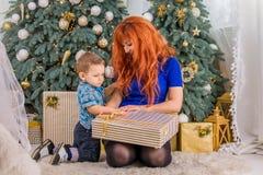 愉快的母亲和她的孩子围拢与圣诞节装饰 图库摄影