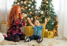 愉快的母亲和她的孩子围拢与圣诞节装饰 免版税库存图片