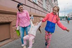 愉快的母亲和她的孩子在城市附近走在一个晴天 库存图片