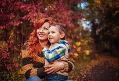 愉快的母亲和她的小儿子走和获得乐趣在秋天森林里 免版税图库摄影