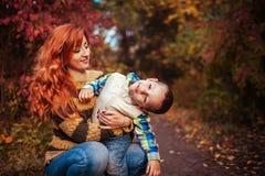愉快的母亲和她的小儿子走和获得乐趣在秋天森林里 库存图片