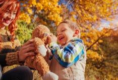 愉快的母亲和她的小儿子走和获得乐趣在秋天森林里 图库摄影