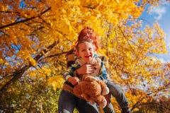 愉快的母亲和她的小儿子走和获得乐趣在秋天森林里 库存照片