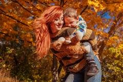 愉快的母亲和她的小儿子走和获得乐趣在秋天森林里 免版税库存照片
