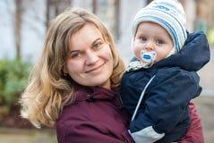 年轻愉快的母亲和她的小男婴在冷的秋天天 库存照片