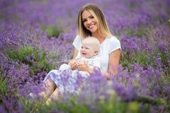 愉快的母亲和她的小男婴获得乐趣在淡紫色领域 免版税库存图片