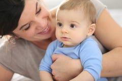 愉快的母亲和她的婴孩在床上 免版税库存图片