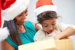 愉快的母亲和孩子圣诞老人帽子的有礼物盒的 免版税图库摄影