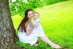 愉快的母亲和孩子坐草在树下在夏天 免版税库存图片