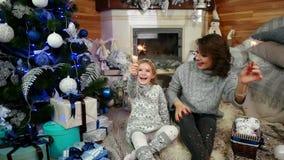 愉快的母亲和孩子有圣诞节烟花的在手、妈妈和女儿升闪烁发光物,家庭位于 影视素材