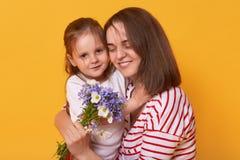愉快的母亲和孩子照片  富感情的女性在紧拿着她的小迷人的女儿 逗人喜爱的孩子给bouguet  库存照片