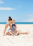 愉快的母亲和孩子看在照片的海滩的秘密审议 免版税库存图片
