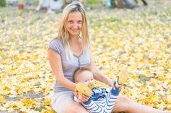 愉快的母亲和小使用与黄色叶子秋天的男婴 库存照片