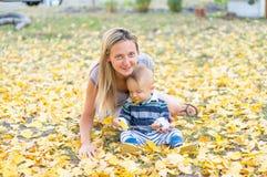 愉快的母亲和小使用与黄色叶子秋天的男婴 免版税图库摄影