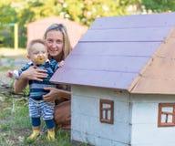 愉快的母亲和小使用与黄色叶子秋天的男婴 免版税库存照片