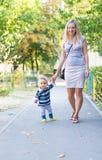 愉快的母亲和小使用与黄色叶子秋天的男婴 库存图片