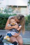 愉快的母亲和小使用与黄色叶子秋天的男婴 图库摄影