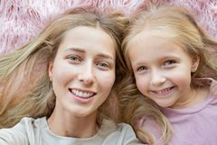愉快的母亲和小女儿有说谎在桃红色毛皮和做selfie的金发的 两美丽的人,家庭观念 免版税图库摄影