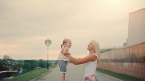 愉快的母亲和小女孩她的胳膊抛的在日落 股票录像