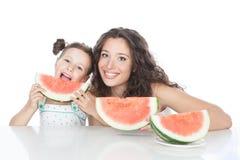 愉快的母亲和小女孩用西瓜 库存照片