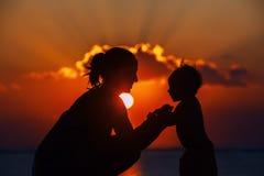 愉快的母亲和快乐的儿子日落剪影 免版税库存照片