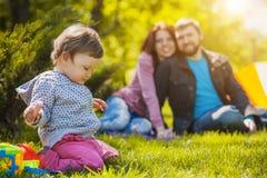 愉快的母亲和父亲plaing与女儿 免版税库存图片