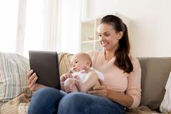 愉快的母亲和男婴有片剂个人计算机的在家 图库摄影