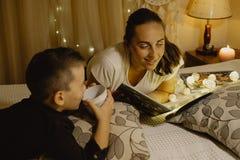 愉快的母亲和男孩在床上的读一本书在去前睡 免版税库存图片