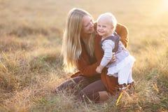 愉快的母亲和笑的使用外面在秋天的女婴 免版税图库摄影