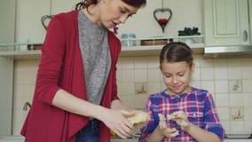 愉快的母亲和逗人喜爱的女儿一起烹调和饮用乐趣活泼的面团在手上在厨房里 家庭,食物,家 影视素材