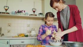 愉快的母亲和逗人喜爱的女儿一起烹调和饮用乐趣活泼的面团在手上 家庭、食物、家和人们 股票录像