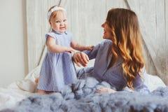 愉快的母亲和9个月大婴孩使用在卧室的配比的睡衣的早晨 库存图片
