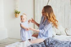 愉快的母亲和9个月大婴孩使用在卧室的配比的睡衣的早晨 图库摄影