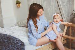 愉快的母亲和9个月大婴孩使用在卧室的配比的睡衣的早晨 免版税库存图片